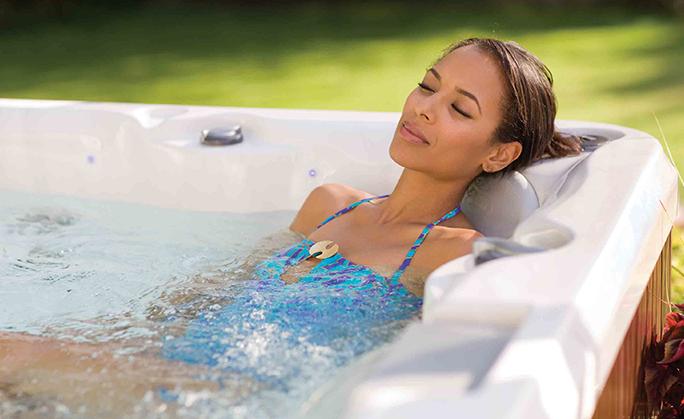 mulher sentada numa banheira de hidromassagem ao ar livre